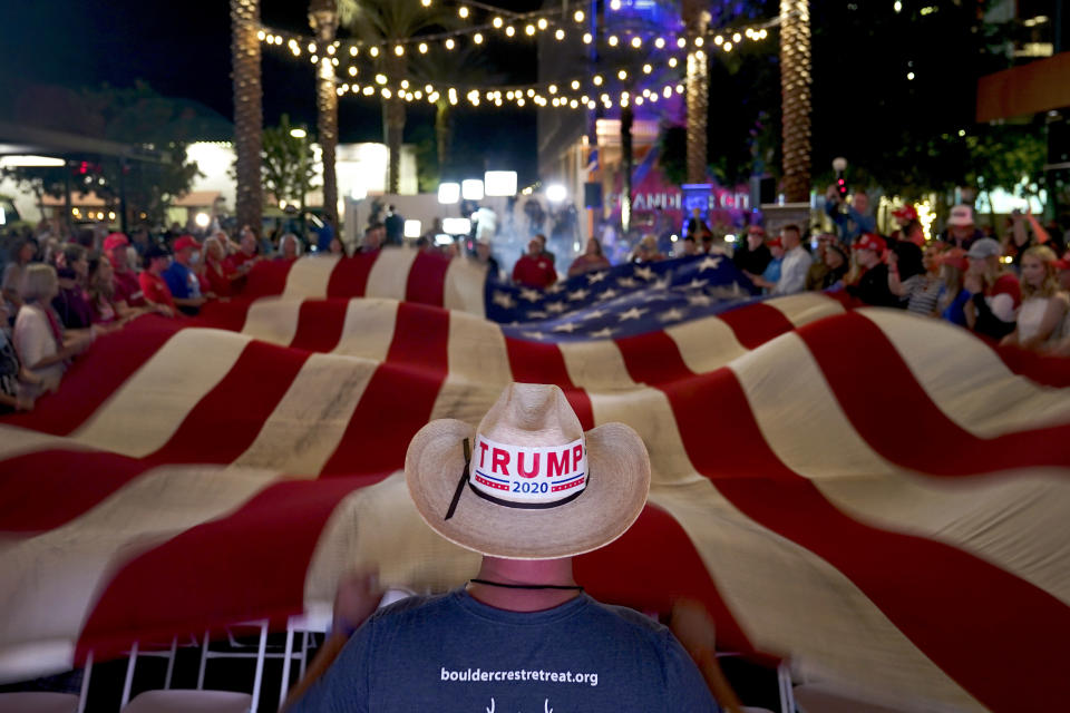 President Donald Trump supporters wave a flag during an election watch party Tuesday, Nov. 3, 2020, in Chandler, Ariz. (AP Photo/Matt York)