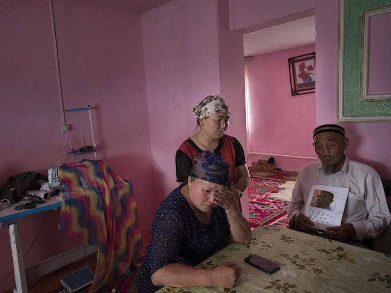 Auelkhan (centre) visits with Gulnar Kosdaulet (left), and Akbar Yenkelesh in their home in Akshi. Kosdaulet's husband, Sarsenbek Akbar, 45, is in a camp in Xinjiang. Yenkelesh, her father-in-law, holds up a photo of his son: Photo for The Washington Post by Joel van Houdt