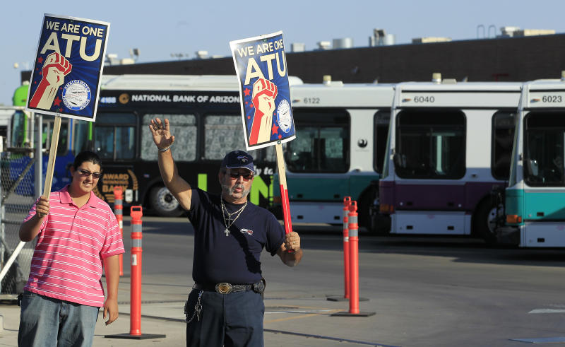 A few dozen bus drivers and family members, including Fernando Rodriguez, left, who has a father that is a bus driver, and George Vargas, who is a bus driver, walk in front of a Phoenix bus depot, as they join more than 600 Phoenix area transit bus drivers who are on strike Saturday, March 10, 2012, in Phoenix.  Veolia Transportation Services and Amalgamated Transit Union Local 1433 failed to end a nearly two-year dispute over wage and benefit terms such as sick-leave accrual, retirement benefits and health care coverage. Drivers walked off the job early Saturday.  Phoenix officials say only about 21 percent of all buses will make their scheduled runs Saturday.(AP Photo/Ross D. Franklin)