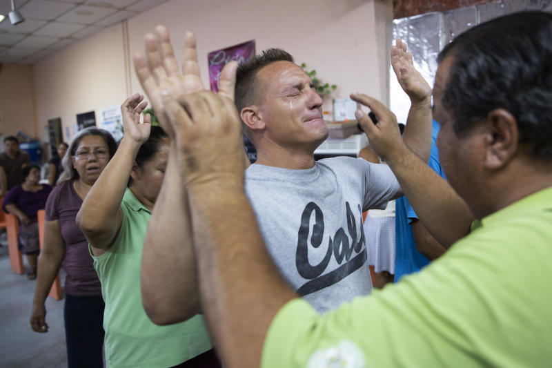 In this July 25, 2019, photo, pastor Juan Fierro, right, touches Miguel, of Cuba, during services at El Buen Pastor shelter for migrants in Cuidad Juarez, Mexico. (AP Photo/Gregory Bull)