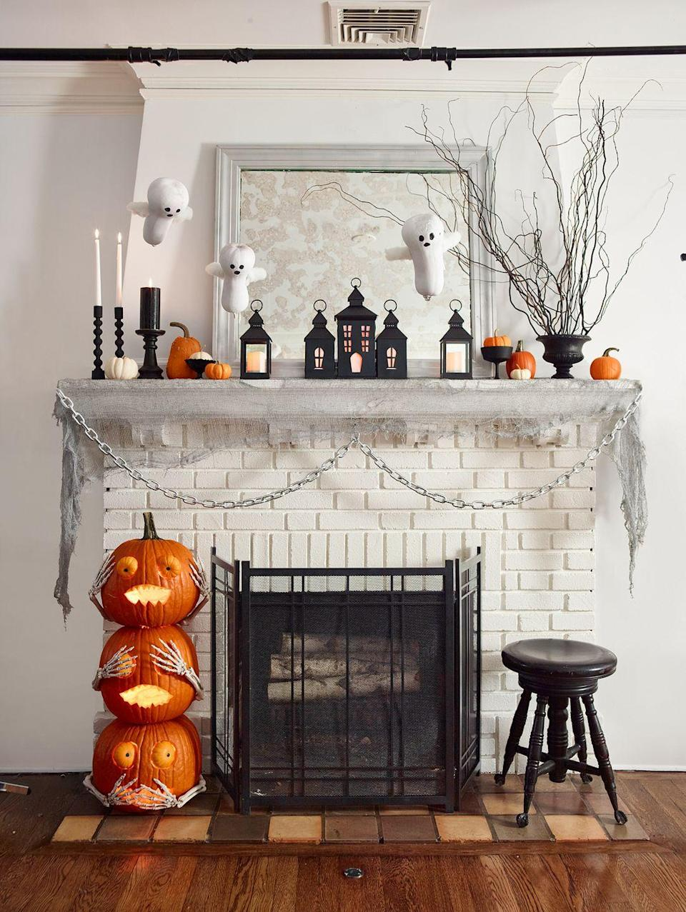 <p>Kids would be impressed with this creepy Halloween mantel display, including hanging ghosts, haunted house lanterns, pumpkins and dark branches.</p>