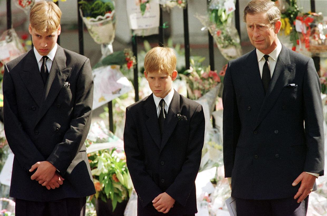 Prince Charles (R), Prince Harry (C) and Prince William look at the coffin of Diana, Princess of Wales, after it was placed into a hearse September 6. Hundreds of thousands of mourners lined the streets of Central London to watch the funeral procession. The Princess died last week in a car crash in Paris.