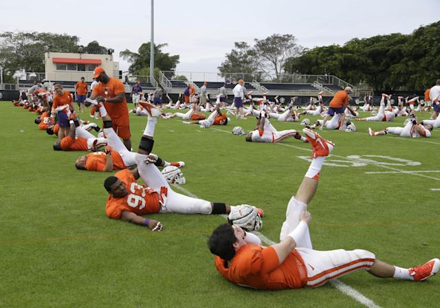Clemson defensive end Corey Crawford (93) and safety Phillip Fajgenbaum, right, stretch during college football practice Monday, Dec. 30, 2013, at Barry University in Miami Shores, Fla. Clemson plays Ohio State in the Orange Bowl Jan. 3. (AP Photo/Lynne Sladky)