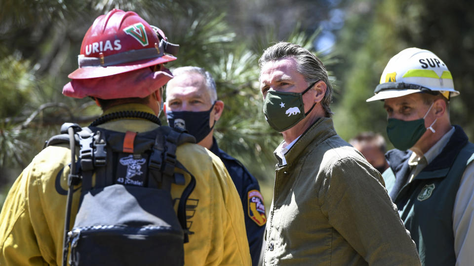 Gov. Gavin Newsom talks with local and state fire officials while touring an area burned by last year's Creek Fire near Shaver Lake in Fresno County, Calif., Thursday, April 8, 2021. California will authorize $536 million for wildfire mitigation and forest management projects before the worst of the fire season strikes later this year, Newsom and legislative leaders said. (Craig Kohlruss/The Fresno Bee via AP)