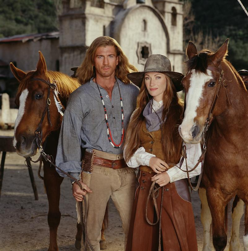 Promotional portrait of British actress Jane Seymour (born Joyce Penelope Wilhelmina Frankenberg), as Dr. Michaela 'Mike' Quinn, and American actor Joe Lando, as Byron Sully, as they pose with horses for the made-for-tv movie 'Dr. Quinn, Medicine Woman: the Movie,' 1999. (Photo by Spike Nannarello/CBS Photo Archive/Getty Images)
