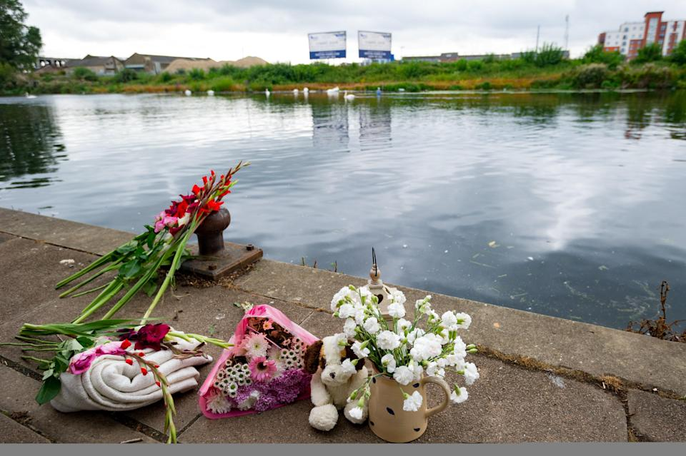 Tributes and flowers are placed at the riverside where Ruby fell in the water (SWNS)
