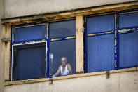 A patient stands by the window at the Emergency Hospital in Calarasi, southern Romania, the former workplace of Claudia Anghel, a Romanian midwife working in England, on Monday, July, 27, 2020. Romania joined the European Union in 2007 and, by 2013, more than 14,000 Romanian doctors were working abroad, about 26% of the country's total number of physicians. (AP Photo/Andreea Alexandru)