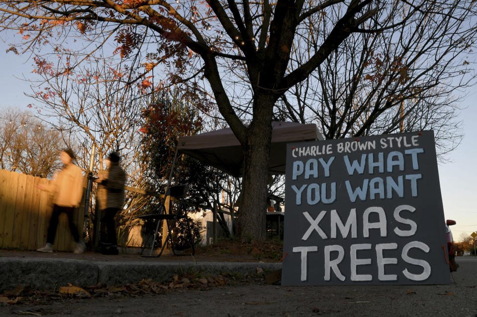 Pedestrians walk by Frank Pichel's tree lot, Sunday, Dec. 6, 2020, in Richmond, Va. A Virginia man has found a way to use Charlie Brown-style Christmas trees to benefit a middle school that provides scholarships for students from an impoverished area. (AP Photo/Will Newton)