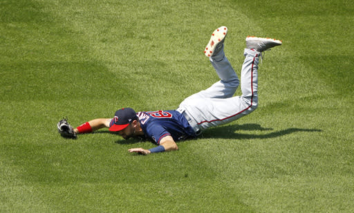 Minnesota Twins center fielder Jake Cave hits the turf after missing the catch of a three-run inside-the-park home run hit by Kansas City Royals' Drew Butera during the seventh inning of a baseball game Sunday, July 22, 2018, in Kansas City, Mo. (AP Phot0/Charlie Riedel)