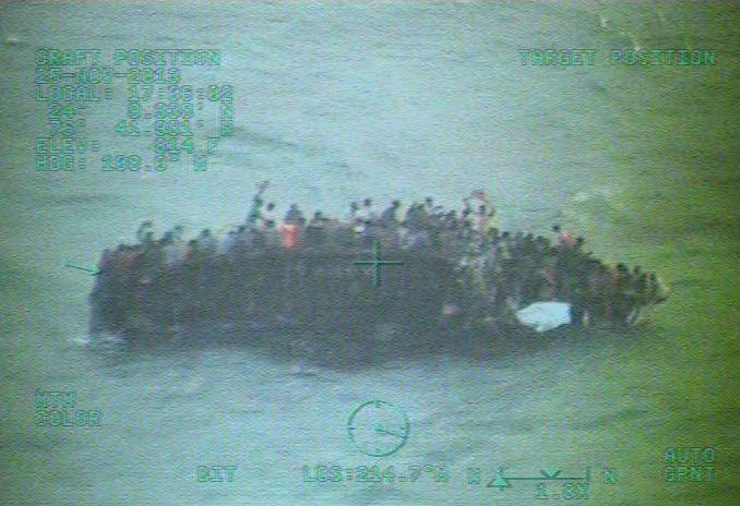 This image taken from video made available by the U.S. Coast Guard shows a group of Haitian migrants sitting on the hull of a capsized sailboat near Staniel Cay, Bahamas, Tuesday, Nov. 26, 2013. Bahamian authorities have confirmed that at least 20 people died when the boat flipped over near Staniel Cay. Interviews with migrants suggest the toll could reach about 30 people. The overloaded sailboat apparently struck a reef and capsized near tiny Harvey Cay, west of Staniel Cay in the Exumas. (AP Photo/U.S. Coast Guard)