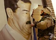 <p>U.S. Marine Major Bull Gurfein pulls down a poster of Iraqi President Saddam Hussein March 21, 2003 in Safwan, Iraq. Chaos reigns in southern Iraq as coalition troops continued their offensive to remove Iraq's leader from power. (Photo by Chris Hondros/Getty Images) </p>