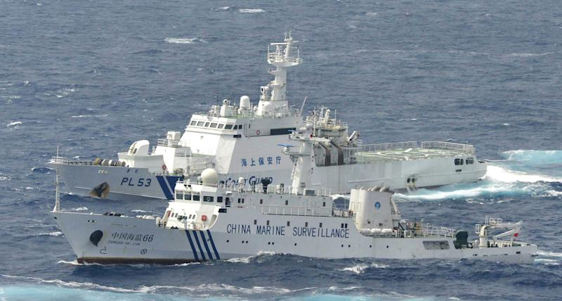 FILE - In this Monday, Sept. 24, 2012 file photo, Japan Coast Guard vessel sails along with Chinese surveillance ship Haijian No. 66, foreground, near disputed islands the Senkaku in Japan and Diaoyu in China, in the East China Sea. China is trying to strengthen its claim on tiny, uninhabited, Japanese-controlled islands by raising questions about the much larger Okinawa chain that is home to more than a million Japanese along with major U.S. military installations. The tactic, however, appears to have done little but harden Tokyo's stance. (AP Photo/Kyodo News, File) JAPAN OUT, MANDATORY CREDIT