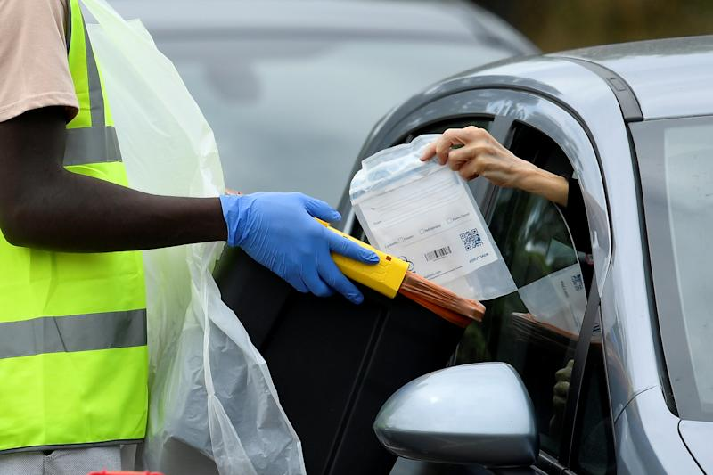 An official collects a testing kit through a car window at a mobile drive through coronavirus disease (COVID-19) testing centre, in Richmond, London, Britain August 4, 2020. REUTERS/Toby Melville