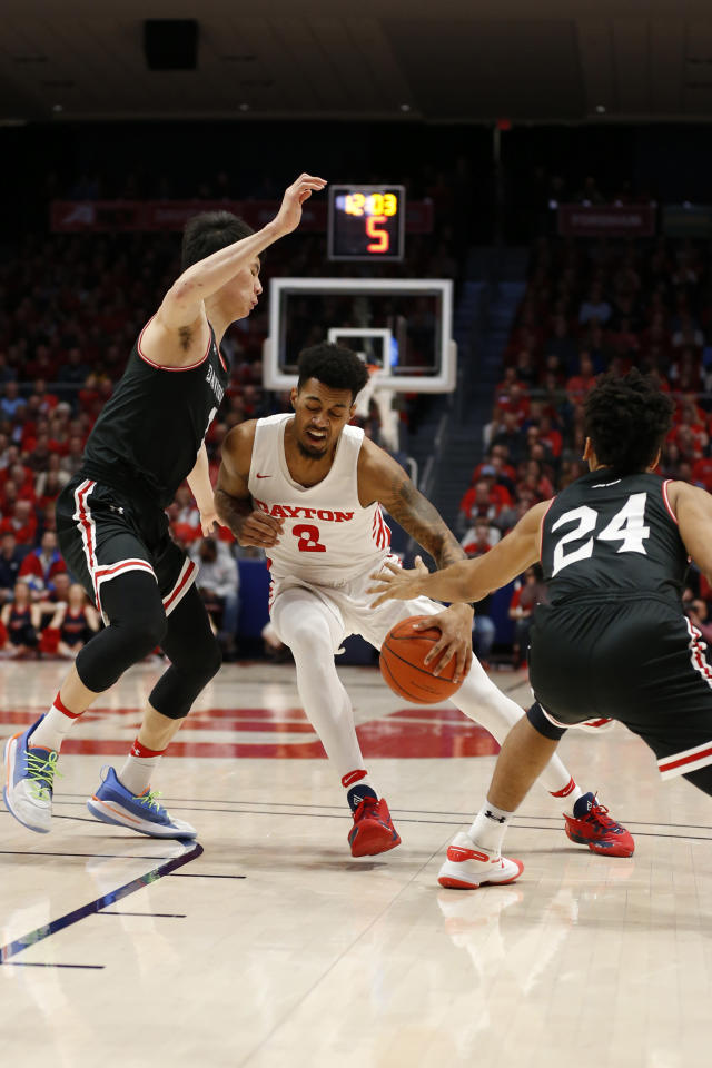 Dayton guard Ibi Watson (2) drives between Davidson forward Hyunjung Lee, left, and guard Carter Collins (24) during the first half of an NCAA college basketball game Friday, Feb. 28, 2020, in Dayton, Ohio. (AP Photo/Gary Landers)