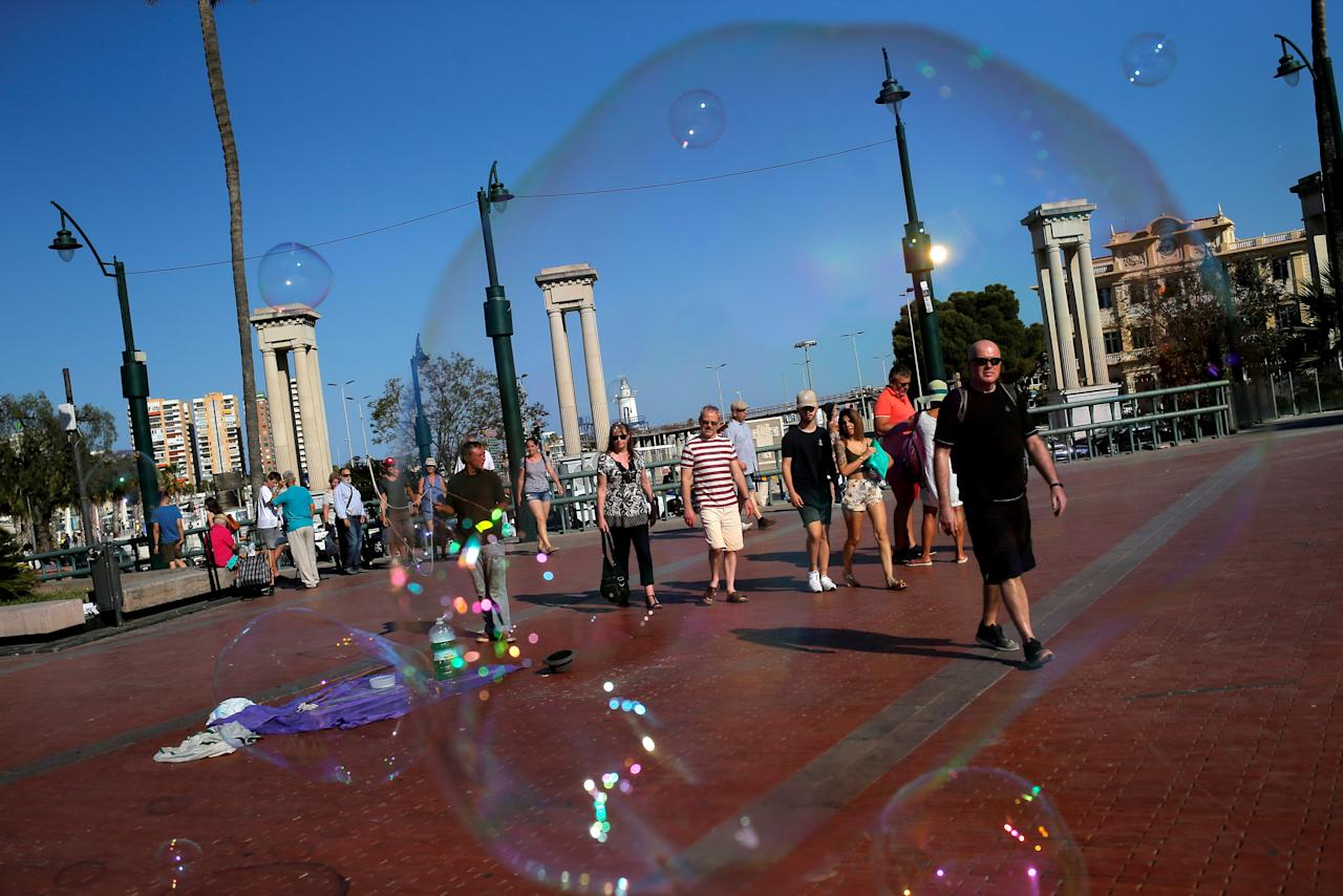 Tourists are pictured through a soap bubble created by a street performer in downtown Malaga, Spain, June 20, 2018. REUTERS/Jon Nazca