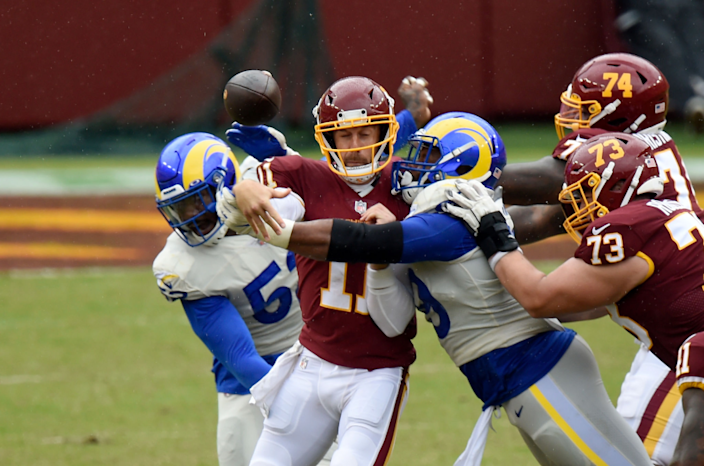 LANDOVER, MD - OCTOBER 11: Alex Smith #11 of the Washington Football Team is hit by Aaron Donald.