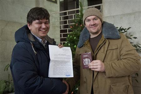 Greenpeace International activist Anthony Perrett (R) from Britain poses with his lawyer Sergey Golubok, who holds papers certifying the termination of prosecution, after he became the first of the 30 Greenpeace Arctic activists to have the criminal case against him dropped, in Saint Petersburg, December 24, 2013, in this handout image courtesy of Greenpeace. REUTERS/Dmitri Sharomov