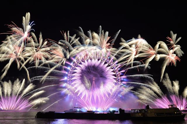 <p>Fireworks light up the sky over the London Eye in central London during the New Year celebrations. (Photo: John Stillwell/PA Images via Getty Images) </p>