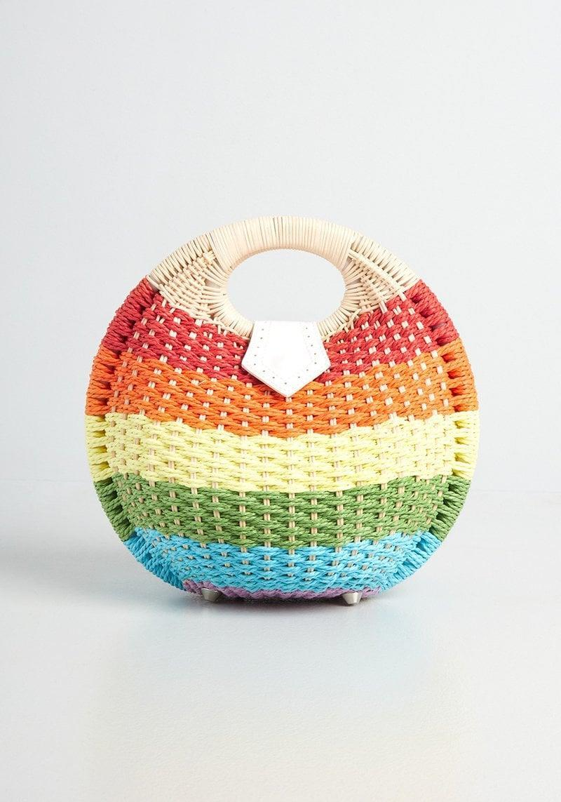 <p>You can't go wrong with this <span>A Basket Full Of Rainbows Bag</span> ($59), it's perfect for the summertime. This structured round handbag is made from natural wicker and has a snap-button tab closure.</p>