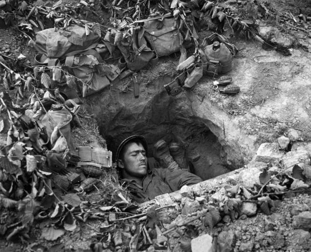 <p>An American GI asleep in a trench in Normandy, France. (Photo: Three Lions/Getty Images) </p>