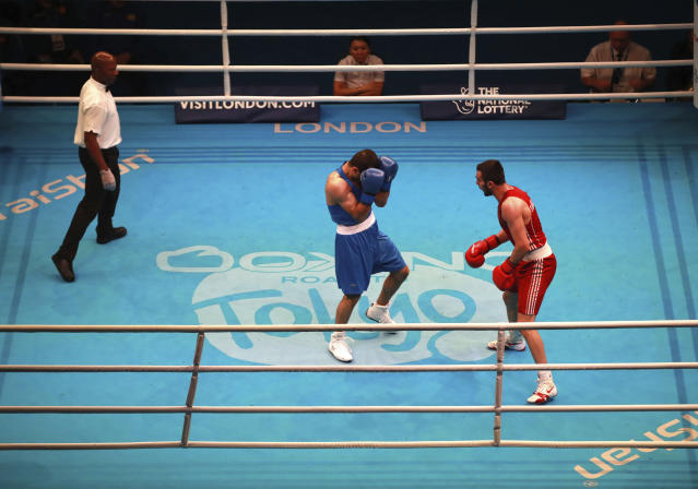A general view of the bout between Turkey's Necat Ekinci, right, and Armenia's Gurgen Madoyan (blue) during day three of the Boxing Road to Tokyo 2020 Olympic qualifying event in London, Monday March 16, 2020. (Adam Davy/PA via AP)