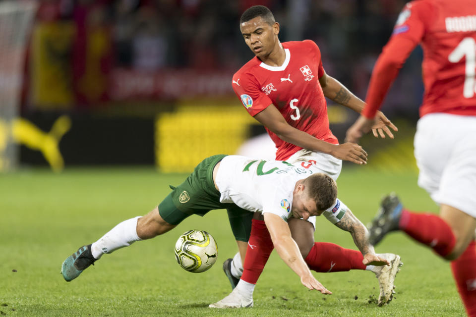 Ireland's forward James Collins, left, clashes with Switzerland's defender Manuel Akanji, top, during their Euro 2020 qualifying Group D soccer match at the Stade de Geneve, in Geneva, Switzerland, Tuesday, Oct. 15, 2019. (Laurent Gillieron/Keystone via AP)