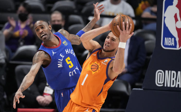 Phoenix Suns guard Devin Booker, right, pulls in a rebound as Denver Nuggets forward Will Barton defends during the first half of Game 3 of an NBA second-round playoff series Friday, June 11, 2021, in Denver. (AP Photo/David Zalubowski)