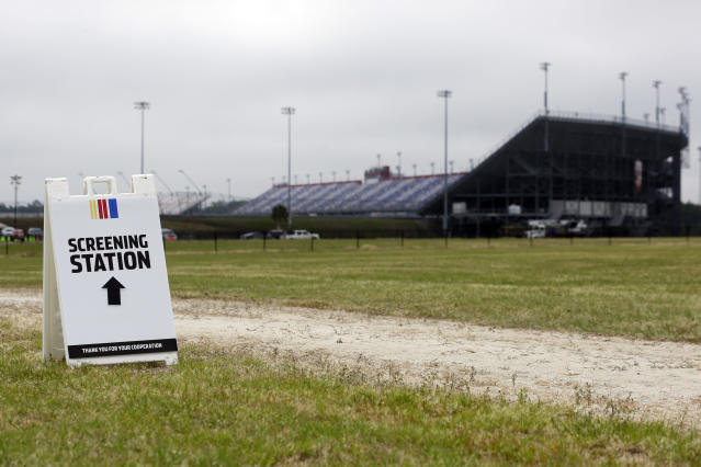 A sign directs people to a screening station outside Darlington Raceway Sunday, May 17, 2020, in Darlington, S.C. NASCAR, which has been idle since March 8 because of the coronavirus pandemic, makes its return with the Real Heroes 400 Nascar Cup Series auto race Sunday. (AP Photo/Brynn Anderson)