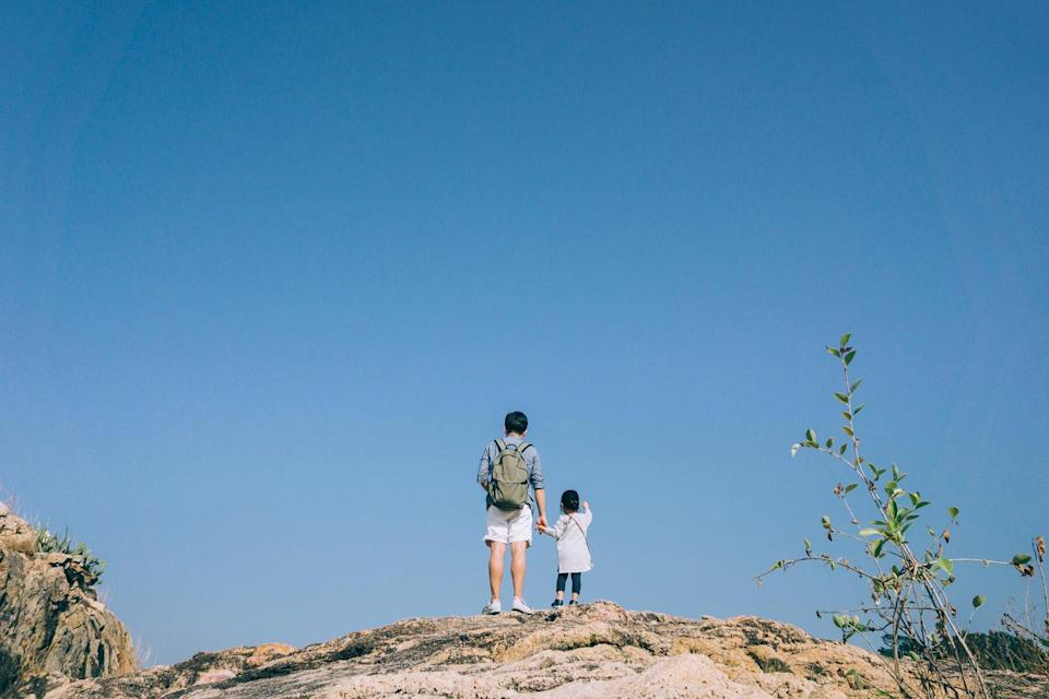 Parent and child standing on a rock against a blue sky
