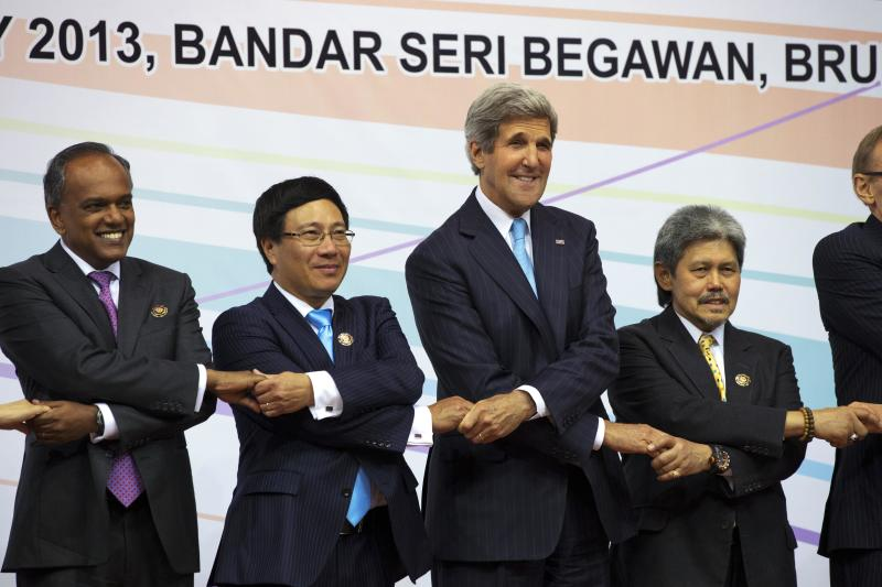 U.S. Secretary of State John Kerry, third from left, participates in a chain handshake during a group photo of foreign ministers during the ASEAN security meetings in Bandar Seri Begawan, Brunei Tuesday, July 2, 2013. Kerry is expected to start the return to Washington Tuesday afternoon. They are from left, Singapore Foreign Minister K. Shanmugam Vietnam's Foreign Minister Pham Binh Minh, Kerry and Brunei Foreign Minister Brunei's Foreign Minister Mohamed Bolkiah. (AP Photo/Jacquelyn Martin, Pool)
