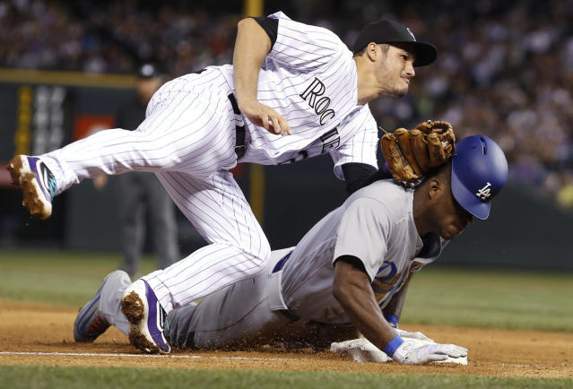 <p>Colorado Rockies third baseman Nolan Arenado, left, tags out Los Angeles Dodgers' Yasiel Puig, who tried to stretch a double into a triple during the sixth inning of a baseball game, May 12, 2017, in Denver. The Dodgers won 6-2. (Photo: David Zalubowski/AP) </p>