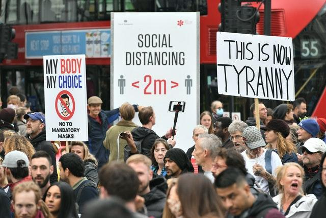 Protesters during an anti-lockdown rally pass a social distancing sign on Tottenham Court Road, London (Dominic Lipinski/PA)
