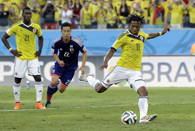 Colombia's Juan Cuadrado scores the opening goal from the penalty spot during the group C World Cup soccer match between Japan and Colombia at the Arena Pantanal in Cuiaba, Brazil, Tuesday, June 24, 2014. (AP Photo/Kirsty Wigglesworth)