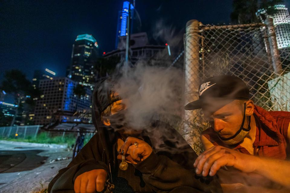 Dee (L) 29 years-old, who was released from the jail because of the Coronavirus pandemic, smokes a pipe loaded with Methamphetamine, while her boyfriend Sean (last name not given) smokes a cigarette next to the 110 Freeway, during the novel Coronavirus, COVID-19, pandemic in Los Angeles California on May 25, 2020. - On May 22, 2020 a federal judge issued a preliminary order requiring that  homeless people living under Los Angeles freeway overpasses and underpasses, be relocated for health and safety reasons. (Photo by Apu GOMES / AFP) (Photo by APU GOMES/AFP via Getty Images)