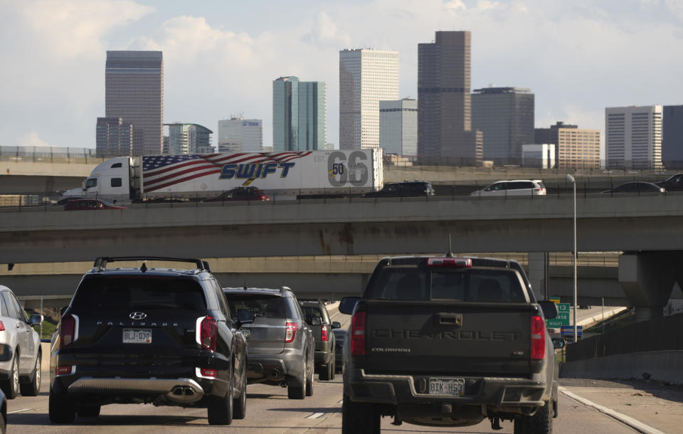 FILE - In this May 27, 2021 file photo, vehicles move along southbound Interstate 25 while motorists sit on the Interstate 70 overpass to start the Memorial Day weekend in Denver. Americans were hitting the road in near-record numbers at the start of the holiday weekend. More than 1.8 million people went through U.S. airports on Thursday, and that number could top 2 million over the weekend, the highest mark since early March of last year. (AP Photo/David Zalubowski)