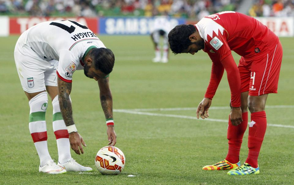 Iran's Ashkan Dejagah (L) places the ball for a free kick next to Bahrain's Sayed Dhiya during their Asian Cup Group C soccer match at the Rectangular stadium in Melbourne January 11, 2015. REUTERS/Brandon Malone (AUSTRALIA - Tags: SOCCER SPORT)