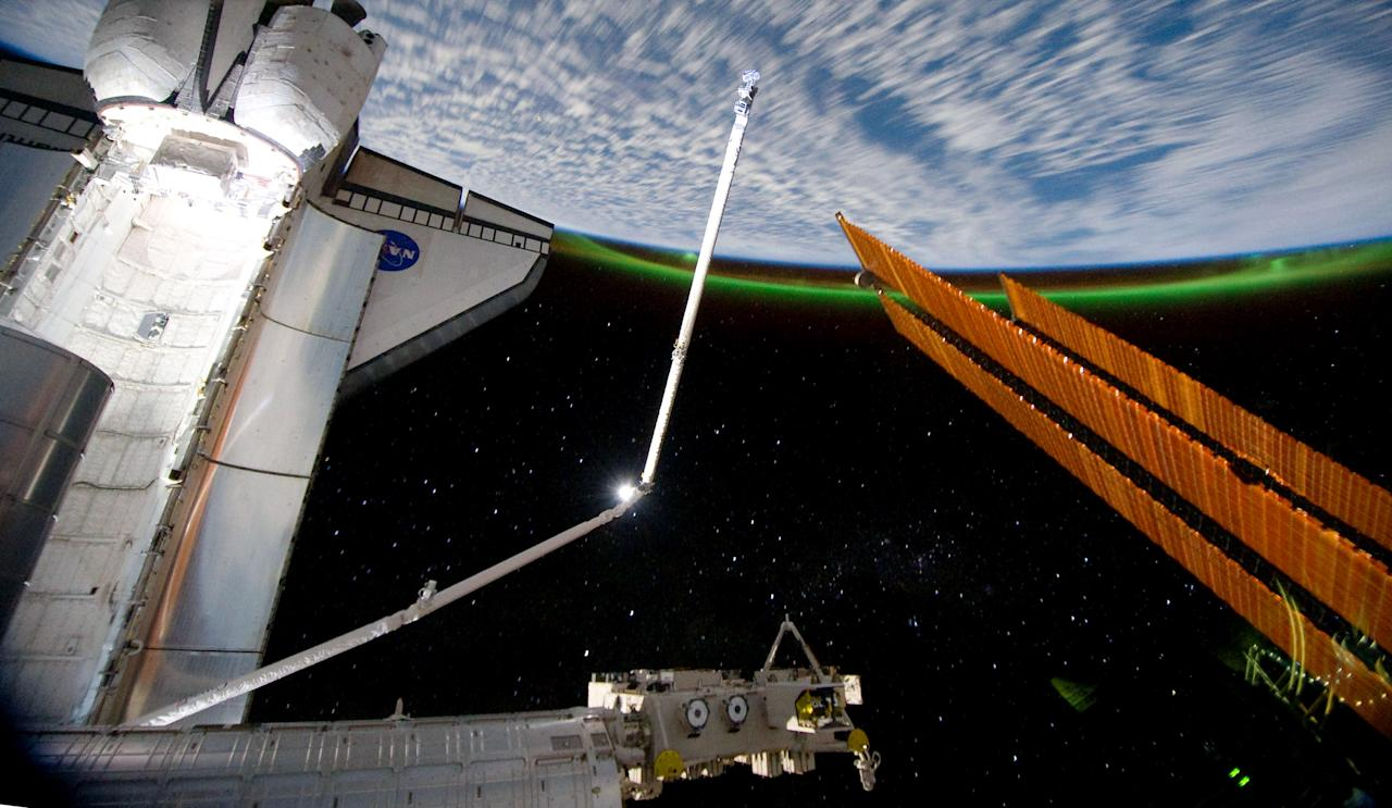 IN SPACE - JULY 14:  In this handout image provided by the National Aeronautics and Space Administration (NASA), the Southern Lights or Aurora Australis ring planet earth as the docked space shuttle Atlantis' cargo bay (L) and the solar array panel of the International Space Station are seen July 14, 2011 in space. Space shuttle Atlantis is on the last leg of a 12-day mission to the International Space Station where it delivered the Raffaello multi-purpose logistics module packed with supplies and spare parts. This was the final mission of the space shuttle program, which began on April 12, 1981 with the launch of Colombia.  (Photo by NASA via Getty Images)