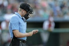 "<span class=""caption"">The home plate umpire checks an iPhone while wearing an earpiece – equipment used to relay automated ball and strike calls – prior to the start of an Atlantic League baseball game in 2019.</span> <span class=""attribution""><a class=""link rapid-noclick-resp"" href=""http://www.apimages.com/metadata/Index/Robot-Umpires-Baseball/f6752f50bb604c4bb001a96aae99a7d2/10/0"" rel=""nofollow noopener"" target=""_blank"" data-ylk=""slk:AP Photo/Julio Cortez"">AP Photo/Julio Cortez</a></span>"