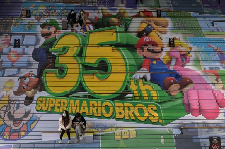"""Eternal evergreen: People sit on stairs before a promotional display for Nintendo's """"Super Mario Bros."""" game in Seoul, South Korea"""