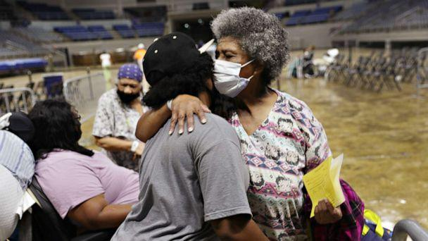 PHOTO: Demeteri Bushnell gets a hug from her great niece as they and other evacuees prepare to board a bus as they are evacuated by local and state government officials before the arrival of Hurricane Laura, on Aug. 26, 2020, in Lake Charles, Louisiana. (Joe Raedle/Getty Images)