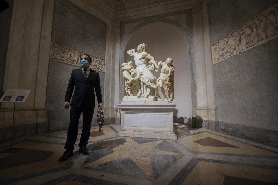 "Gianni Crea, the Vatican Museums chief ""Clavigero"" key-keeper, walks past the Laocoon statue, a masterpiece of the sculptors of Rhodes dated around 40-30 B.C., on his way to open the museum's rooms and sections, at the Vatican, Monday, Feb. 1, 2021. Crea is the ""clavigero"" of the Vatican Museums, the chief key-keeper whose job begins each morning at 5 a.m., opening the doors and turning on the lights through 7 kilometers of one of the world's greatest collections of art and antiquities. The Associated Press followed Crea on his rounds the first day the museum reopened to the public, joining him in the underground ""bunker"" where the 2,797 keys to the Vatican treasures are kept in wall safes overnight. (AP Photo/Andrew Medichini)"