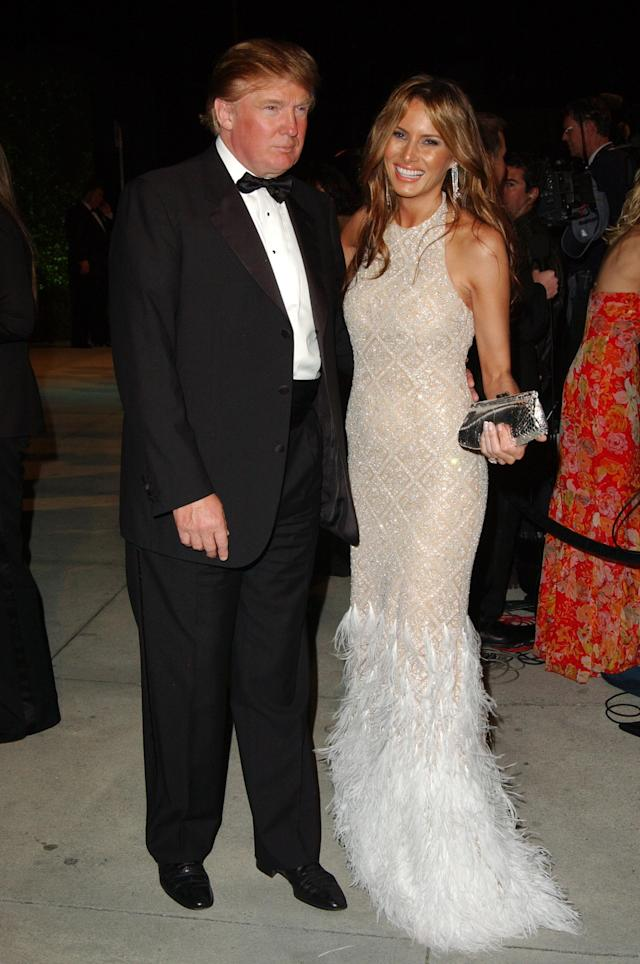 <p>Melania wore a feather-embellished gown in 2005. She paired the elegant dress with stunning long diamond earrings and a silver clutch. Arguably, her striking smile is her best accessory. (Photo: Getty Images) </p>