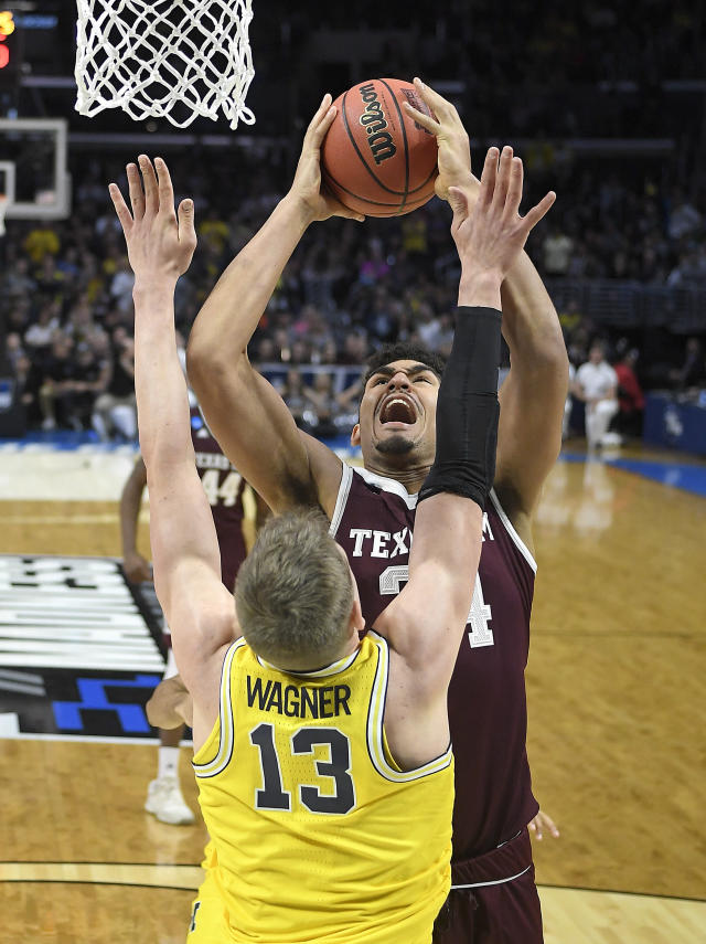 Texas A&M center Tyler Davis shoots against Michigan forward Moritz Wagner (13) during the first half of an NCAA men's college basketball tournament regional semifinal Thursday, March 22, 2018, in Los Angeles. (AP Photo/Alex Gallardo)