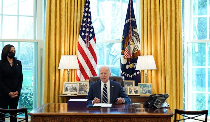 US President Joe Biden, with Vice President Kamala Harris, prepares to sign the American Rescue Plan on March 11, 2021, in the Oval Office of the White House in Washington, DC. - Biden signed the $1.9 trillion economic stimulus bill and will give a national address urging