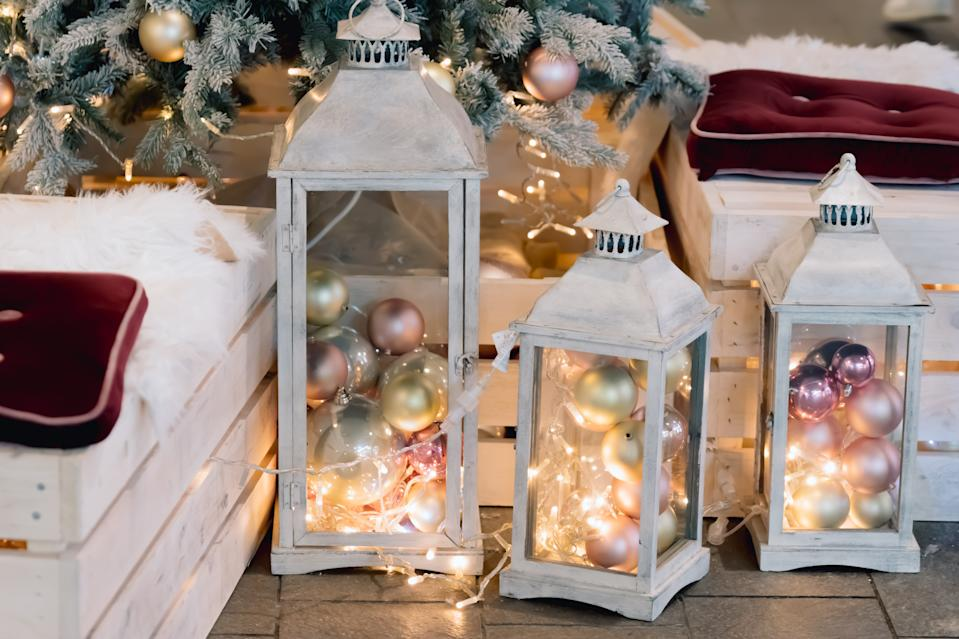 Lantern with holiday baubles on decorated christmas tree background in living room interior. Winter time and lamp on wooden sofa near christmas tree. Cozy vintage holiday home interior