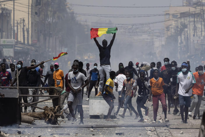 A demonstrator holds up a Senegalese flag during protests against the arrest of opposition leader and former presidential candidate Ousmane Sonko in Dakar, Senegal, Friday, March 5, 2021. Days of violent protests in Senegal have killed at least one person, local reports say, as young people take to the streets nationwide in support of the main opposition leader who was detained Wednesday. (AP Photo/Leo Correa)