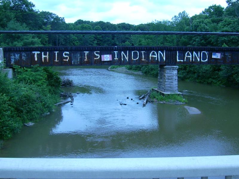 A bridge with the graffiti, 'This is Indian Land' over a river.
