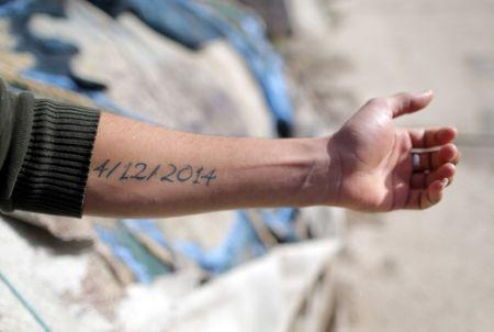 Mutassim al-Misrati, a Benghazi-local who lost his leg during a three-year war in the city, shows his forearm with the date of his wound written on it, in Benghazi, Libya December 27, 2017. Picture taken December 27, 2017. REUTERS/Esam Omran Al-Fetori