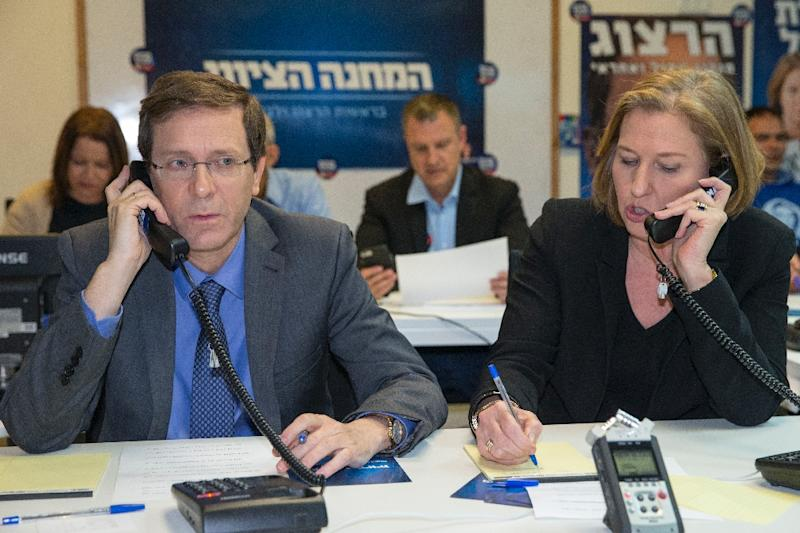 Israeli co-leaders of the Zionist Union list for the upcoming general election -- Labour Party leader, Isaac Herzog (left) and Tzipi Livni -- talk on the phone at the party headquarters in Tel Aviv, on March 15, 2015 (AFP Photo/Jack Guez)