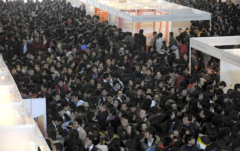 Job seekers crowd booths at a job fair in Beijing, China, on February 7, 2009 (AFP Photo/Liu Jin)